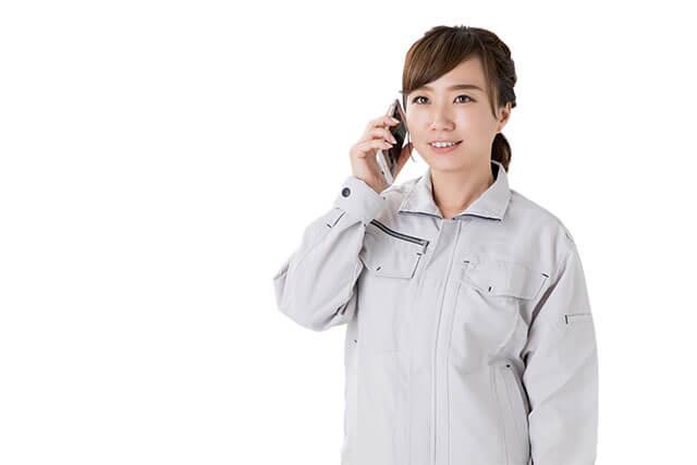 スマートフォンで問い合わせをする若い作業服姿の女性