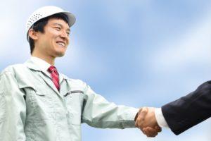 コンサルタントと握手を交わす作業服の従業員