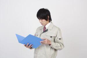 書類を読んで勉強をする作業服姿の若い従業員