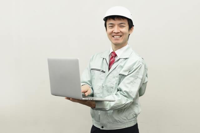 パソコンを操作する作業服・ヘルメット姿の従業員