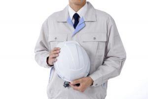 ヘルメットを抱える作業服姿の男性