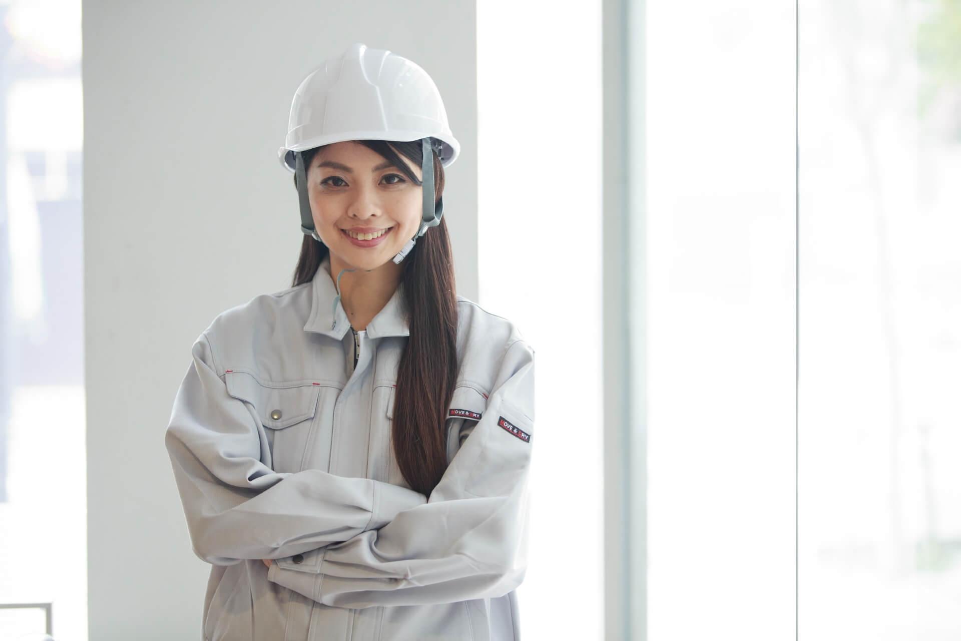 ヘルメットと作業服姿で腕組みをする若い女性従業員