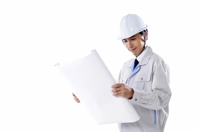 図面を見て現場を点検する作業服・ヘルメット姿の中堅写真