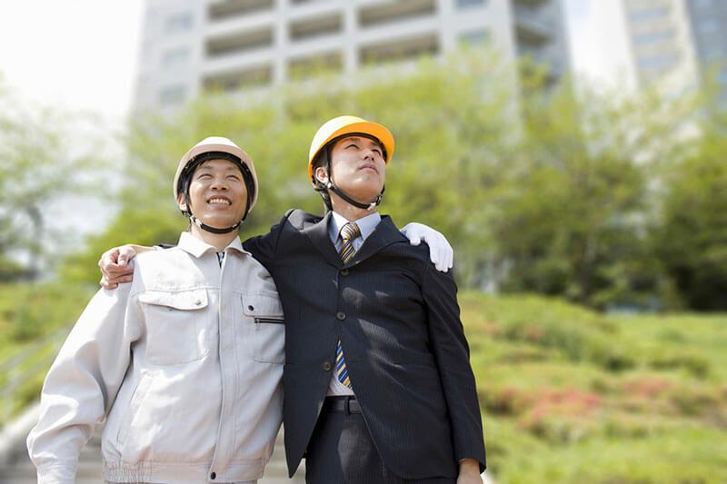 肩を組む作業服姿の従業員とスーツ姿のコンサルタント