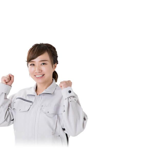 ガッツポーズをする作業服姿の女性